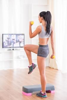 A jovem mulher está exercitando com pesos e etapa em casa.