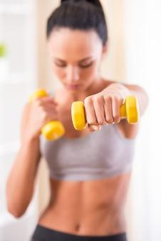 A jovem mulher está exercitando com pesos em casa.