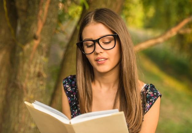A jovem mulher está lendo um livro ao sentar-se no parque.