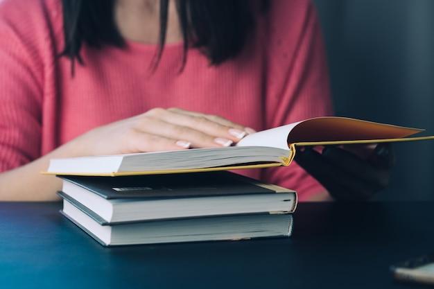 A jovem mulher está lendo um livro em casa. fundo desfocado. horizontal, efeito de filme.