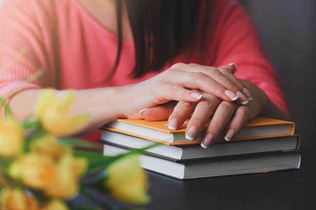 A jovem mulher está lendo um livro em casa.