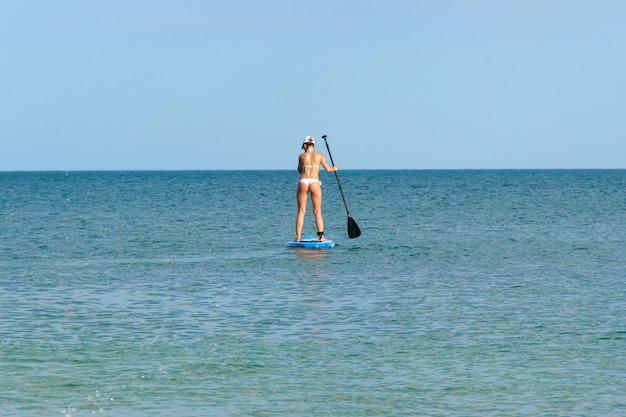 A jovem mulher está paddleboarding na água azul. gaste seu tempo livre ativamente. tenha ótimas férias de verão à beira-mar