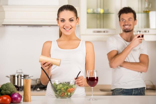 A jovem mulher está preparando a salada vegetal na cozinha.