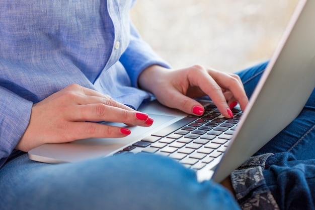 A jovem mulher está sentada no peitoril da janela e trabalhando no laptop