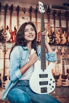 A jovem mulher está sentando-se com a guitarra elétrica na loja da música.