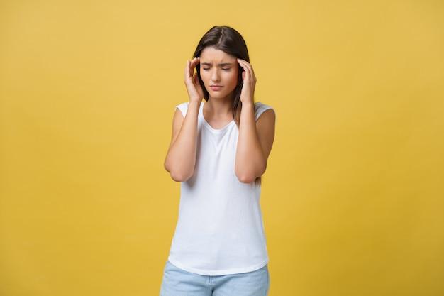 A jovem mulher está sofrendo de uma dor de cabeça contra um fundo amarelo.
