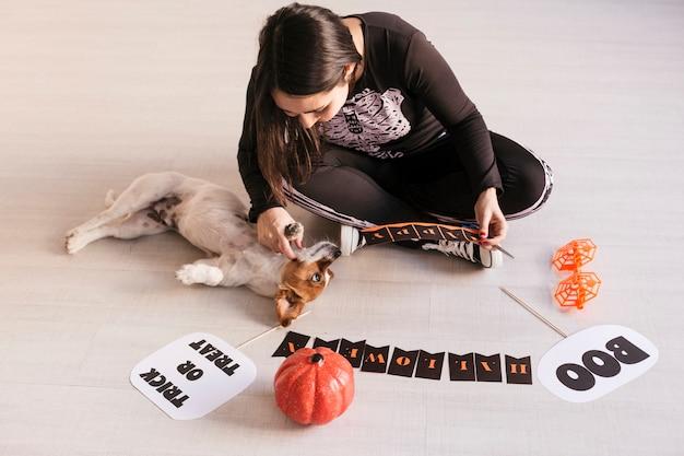 A jovem mulher faz a guirlanda de halloween. diy criativo. festa de projeto de decoração para casa. cão pequeno cuet além