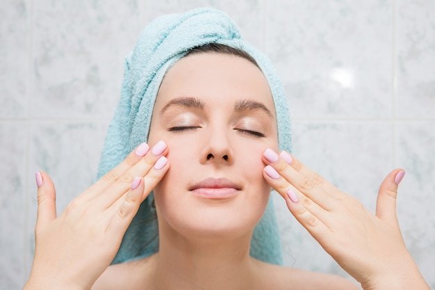 A jovem mulher faz a massagem facial com mãos no banheiro.