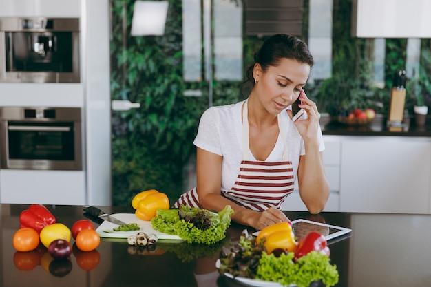 A jovem mulher feliz com avental falando no celular e olhando a receita no tablet na cozinha