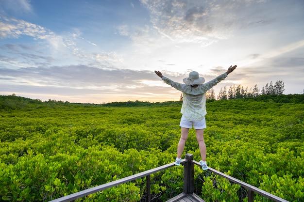 A jovem mulher feliz com mãos levanta-se na paisagem bonita da floresta dos manguezais com céu bonito.