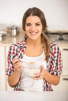 A jovem mulher feliz está comendo o muesli em uma cozinha.