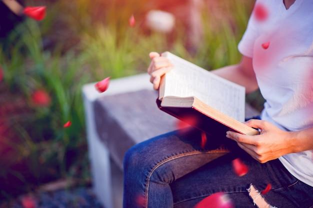 A jovem mulher feliz lendo o livro sozinha