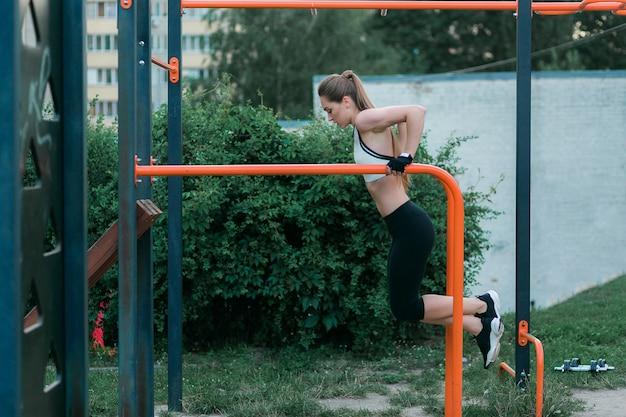 A jovem mulher forte e fisicamente cabida que faz o tríceps mergulha em barras paralelas no parque.