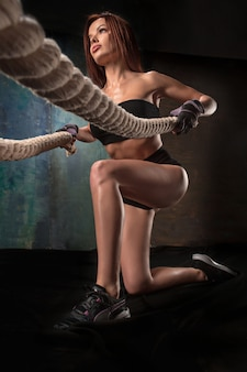 A jovem mulher forte, puxando a corda em uma academia