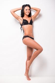 A jovem mulher impressionante está levantando na roupa interior preta.
