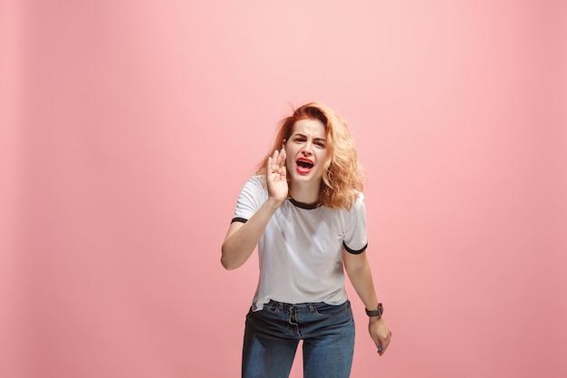 A jovem mulher irritada emocional gritando no fundo rosa studio