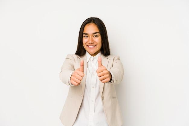 A jovem mulher isolada em uma parede branca com polegares levanta, elogios sobre algo, apoia e respeita o conceito.