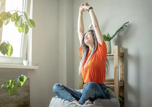 A jovem mulher moderna está sentada em uma espreguiçadeira ao lado da janela e se espreguiçando