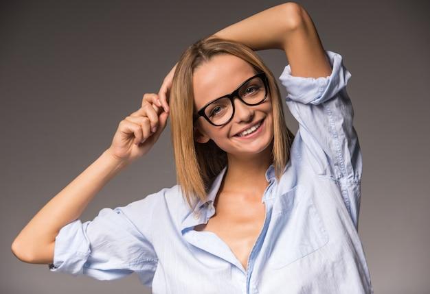 A jovem mulher na camisa e nos vidros está guardando as mãos na cabeça.