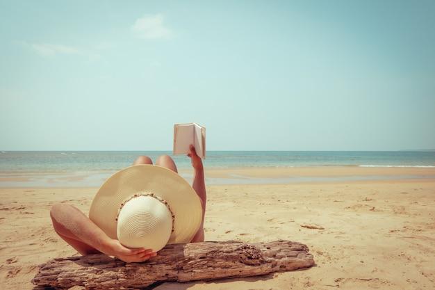 A jovem mulher no encontro do chapéu de palha toma sol em uma praia tropical, relaxa com livro.