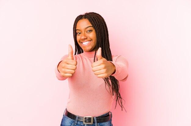 A jovem mulher no rosa com polegares levanta, felicidades sobre algo, apoia e respeita o conceito.