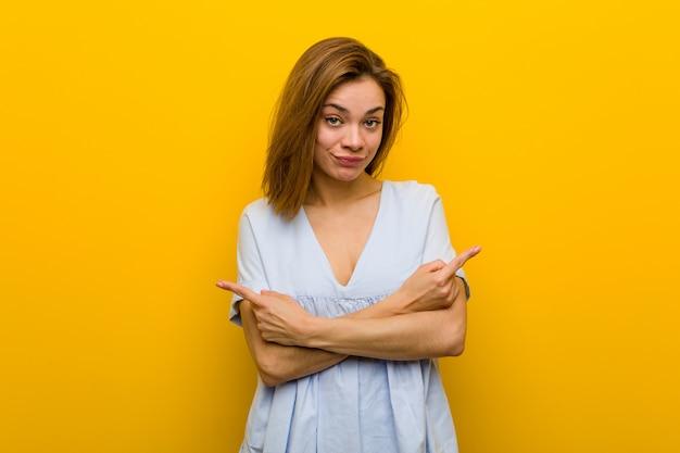 A jovem mulher nova bonita aponta lateralmente, está tentando escolher entre duas opções.