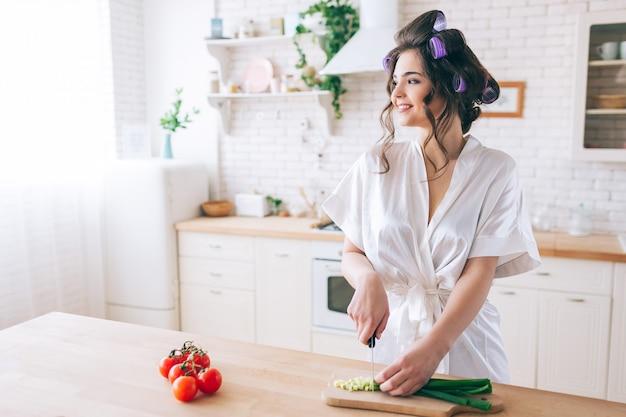A jovem mulher positiva alegre está na cozinha e olha a janela. corte a cebola verde na mesa. governanta feminina usar roupão branco. sozinho na cozinha. pimenta vermelha no lado esquerdo.