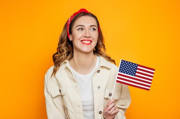 A jovem mulher prende uma bandeira americana pequena e sorrisos isolados sobre o fundo alaranjado