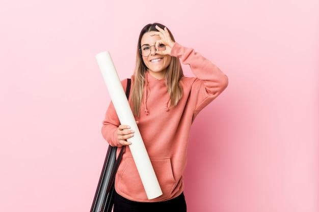 A jovem mulher que estuda a arquitetura excitou mantendo o gesto aprovado no olho.