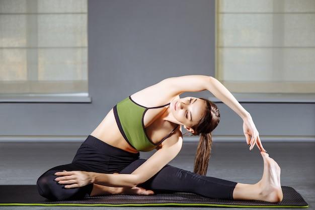 A jovem mulher que faz o esticão exercita no estúdio. ioga