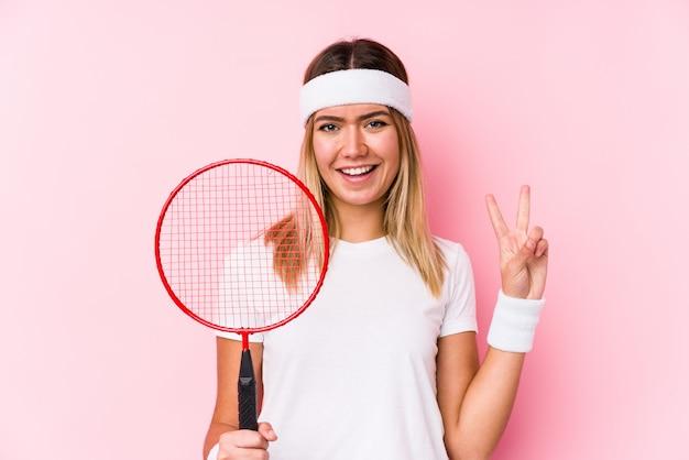 A jovem mulher que joga o badminton isolou mostrar o número dois com dedos.