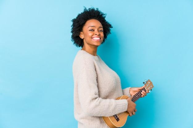 A jovem mulher que joga ukelele olha de lado sorrindo, alegre e agradável