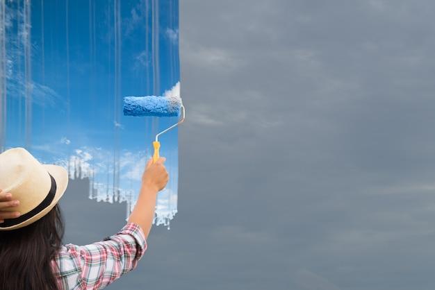 A jovem mulher que pinta o céu cinzento torna-se azul. mudar o conceito.
