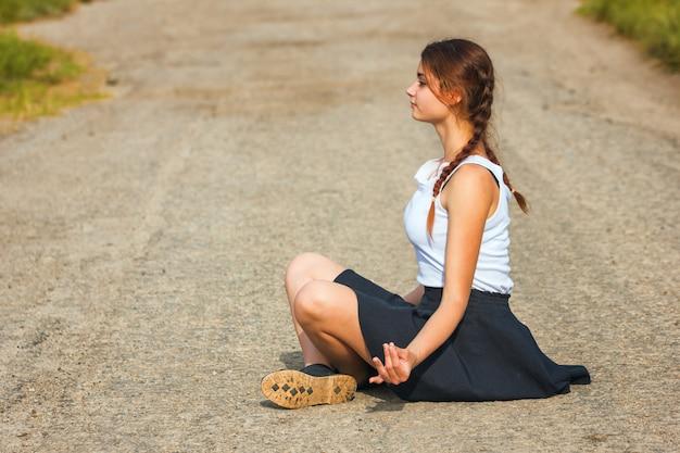 A jovem mulher que senta-se na estrada e que medita, relaxa.