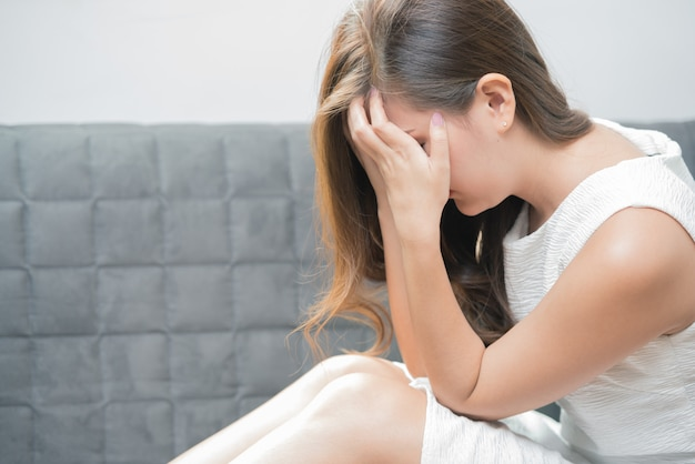 A jovem mulher que senta-se no sofá com mãos fechou sua cara e sentimento triste.