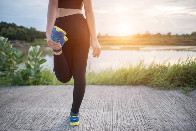 A jovem mulher saudável que aquece fora treina antes de treinar a sessão no parque.