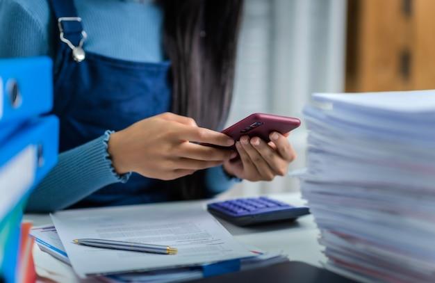 A jovem mulher se cansou de trabalhar com a pilha de papéis, relatórios financeiros, contador e serviço fiscal.