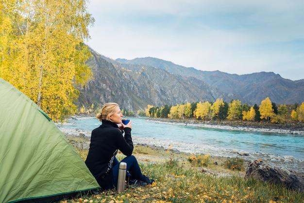 A jovem mulher senta-se na grama perto da barraca do turista e bebe chá / café quente do copo de garrafa térmica na floresta com rio e montanhas.