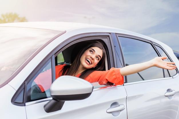 A jovem mulher sentada em um carro distribui pela janela.