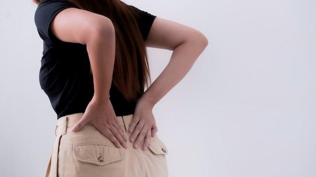 A jovem mulher sofre da dor nas costas, conceito da síndrome do escritório.