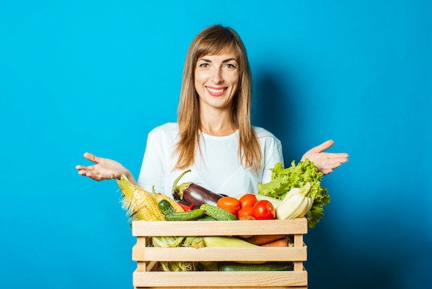 A jovem mulher sorri e prende uma caixa com legumes frescos no azul. bom conceito de colheita, produto natural