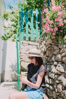 A jovem mulher toma uma foto da vista bonita na vila velha em cinque terre, liguria, itália.