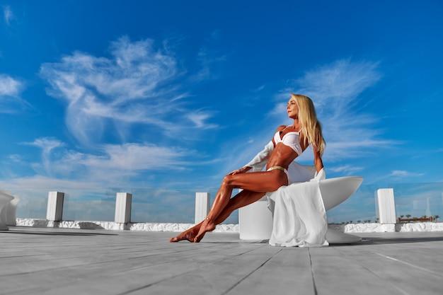 A jovem mulher vestida de branco em um terraço e o céu azul em um fundo