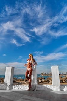 A jovem mulher vestida de branco em um terraço e o céu azul em um fundo Foto Premium