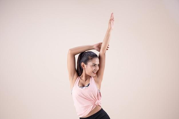 A jovem mulher vestindo roupa de exercício, levantando as mãos no ar, fazendo exercícios de dança