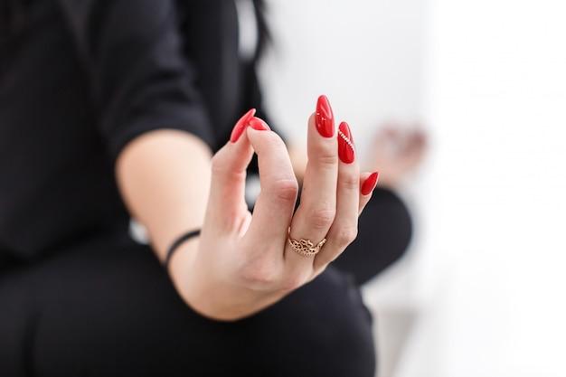 A jovem mulher vestiu-se no terno de negócio preto que senta-se na posição de lótus em um assoalho no escritório, dedos com manicure vermelho dobrados no close-up do mudra.