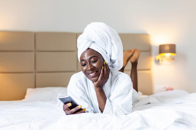 A jovem negra atraente em roupão e com uma toalha na cabeça está segurando o telefone móvel, mensagens de texto e sorrindo enquanto está sentado em uma cama.