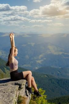 A jovem no topo da montanha levantou as mãos sobre o fundo do céu azul. a mulher subiu ao topo e aproveitou seu sucesso