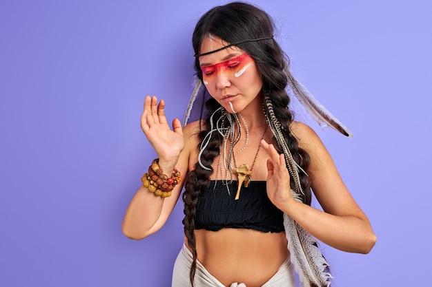 A jovem pagã é uma xamã isolada na parede roxa, as pessoas são diferentes das outras