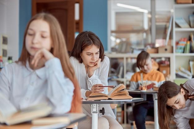 A jovem parece distraída na leitura. crianças do ensino fundamental sentadas em mesas e lendo livros em sala de aula.
